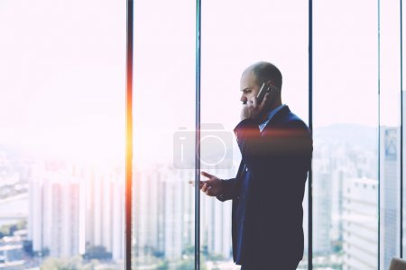 Foto de Serious man CEO dressed in suit having unpleasant mobile phone conversation, while is standing near office window background with copy space for your advertising text message or promotional content - Imagen libre de derechos