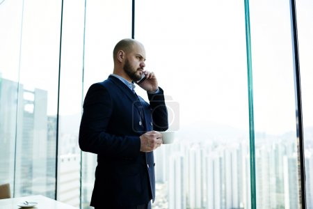 Photo pour Young man successful entrepreneur in suit is phoning via his cell telephone during coffee break in work day, while is standing near office window with view of business district with tall skyscrapers - image libre de droit