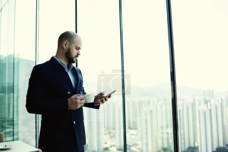 Foto de Man skilled financier is reading financial news in network on mobile phone during coffee break in work day - Imagen libre de derechos