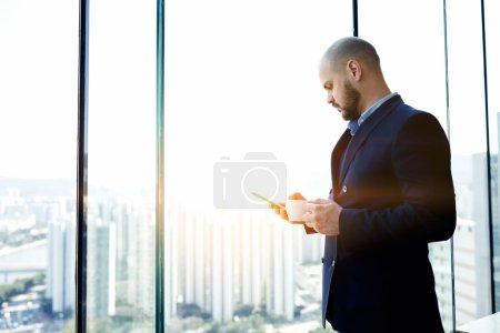 Foto de El hombre emprendedor confiado a través del teléfono móvil está reservando un hotel en línea para su futuro viaje de negocios al extranjero, mientras que está de pie con una taza de café en el interior de la oficina contra ventana con espacio de copia - Imagen libre de derechos