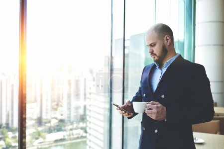 Foto de Confident businessman in luxury suit is reading on cell telephone text message from mobile operator. Managing director is standing with cup of coffee in office near window with metropolitan city view - Imagen libre de derechos