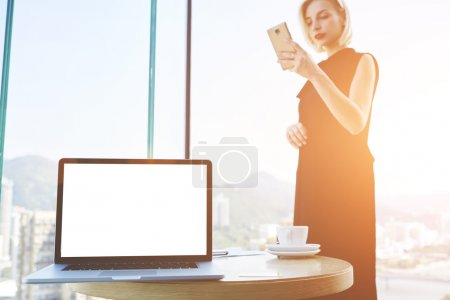 Young confident woman is using mobile phone during work break