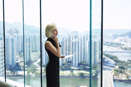 Young female CEO is calling via mobile phone, while is standing near office window with copy space