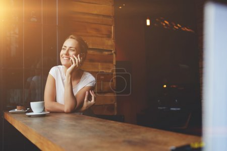 Smiling hipster girl calling with cell telephone while relaxing after walking in summer day