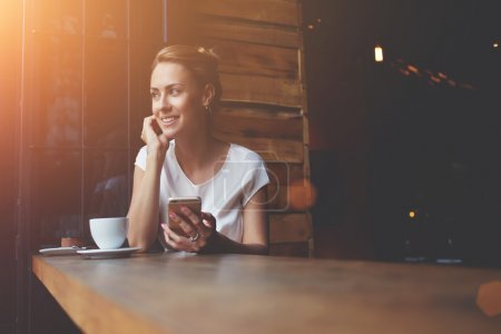 Happy European female using cell telephone while relaxing in modern coffee shop after work day