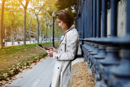 Female dressed in spring clothes is reading information in internet via digital tablet