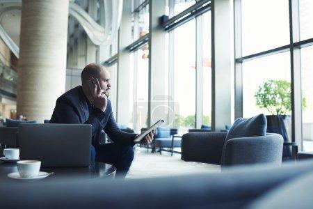 Foto de Empresario confiado con tableta digital en la mano teniendo conversación de teléfono móvil con el administrador de su hotel - Imagen libre de derechos