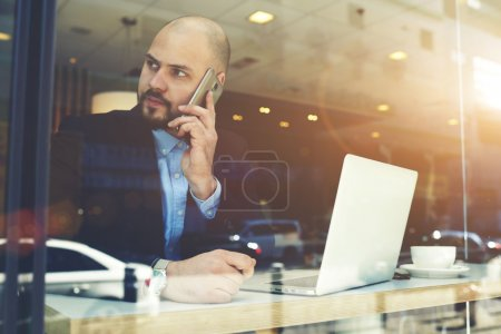 Male entrepreneur phoning via cell telephone