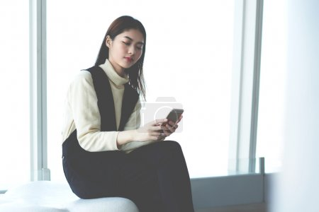 Young businesswoman reading text message