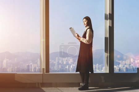 Photo pour Young Asian businesswoman is using digital tablet for searching needed information for upcoming conference, while is standing in office interior against big window with city view on background - image libre de droit