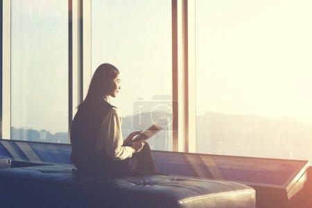 Foto de Chica joven asiática hipster es la celebración de touch pad, mientras está sentado en un interior moderno contra la ventana con vistas a la ciudad - Imagen libre de derechos