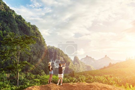 Two female is making photo on mobile phone,  while is standing against jungle landscape and cloudy sky background with copy space