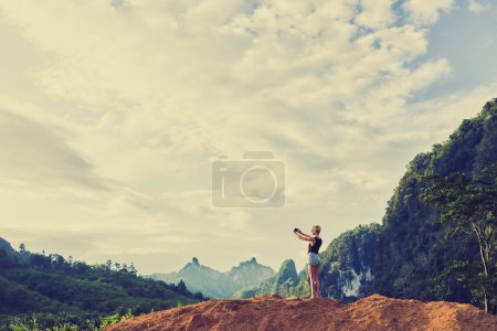Photo pour Touristique de femme prend photo sur le téléphone cellulaire du coucher du soleil de jungle magnifique paysage au cours de l'incroyable voyage d'été - image libre de droit
