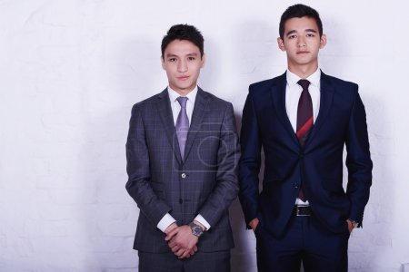 Photo pour Deux jeunes hommes d'affaires asiatiques habillés en costumes posent pour la caméra pendant la pause de travail, tandis que sont debout dans l'intérieur du bureau contre le mur avec de l'espace de copie pour votre message texte publicitaire - image libre de droit