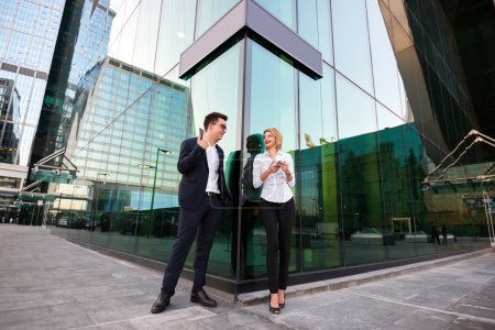 Photo pour Patrons joyeux hommes et femmes vêtus de vêtements d'entreprise avec des téléphones cellulaires dans les mains debout à l'extérieur contre gratte-ciel bâtiment - image libre de droit