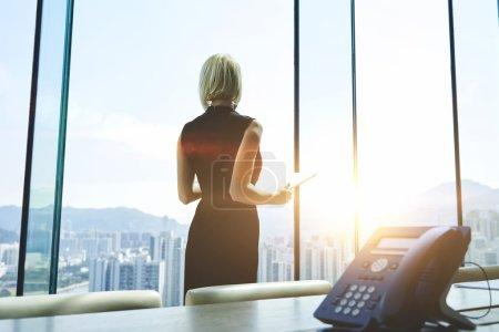 Photo pour Vue arrière d'une femme d'affaires avec tablette numérique dans les mains regarde dans la fenêtre du bureau et de penser à l'avenir de son entreprise. Gestionnaire féminin utilise pavé tactile pendant la journée de travail - image libre de droit