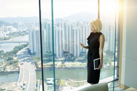 Foto de Confident young female financier with touch pad in hand is reading financial news in network via mobile phone, while is standing near private office window with view of high buildings business district - Imagen libre de derechos