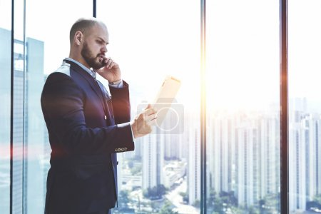 Photo for Young man proud CEO analyzing activity of the company via digital tablet and talking with financial manager during his business trip, while is standing near office window with copy space - Royalty Free Image