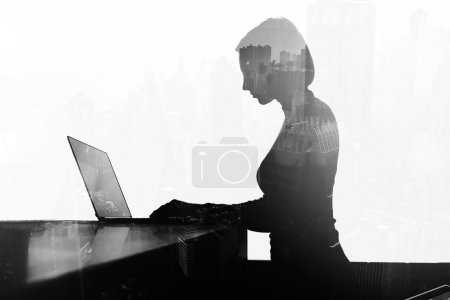 Young businesswoman is keyboarding on net-book at office desktop