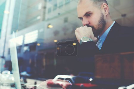 Confident businessman with serious face is using net-book during coffee break