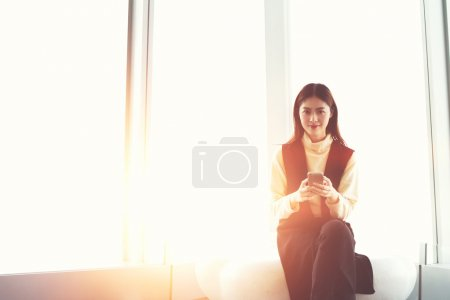 Young charming Japanese businesswoman with mobile phone in hands is looking at camera