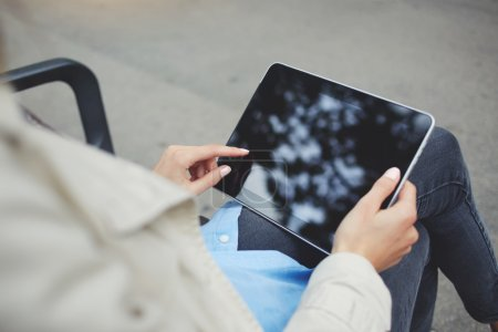 Closely image of hipster girl is chatting in social network via touch pad, while is relaxing in the fresh air during free time