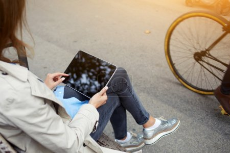 Back view of young hipster girl is making purchase at the on-line store via touch pad, while is sitting on the street in spring day