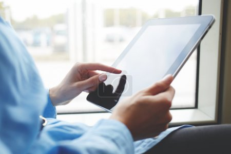 Closeup image of woman is booking on-line via portable digital tablet. Closely of female is searching needed file on her touch pad with copy space screen.