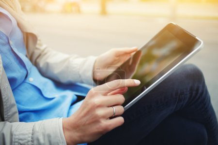 Closeup image of woman is watching photos on portable touch pad during her recreation time in weekend.