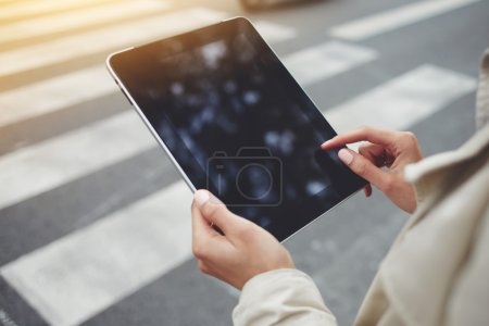 Closely image of woman`s hand is holding digital tablet with copy space screen for your advertising text message or promotional content.