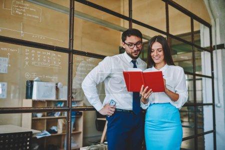 Foto de Exitosos profesionales masculinos y femeninos de 30 años que leen la comprobación de la información del bloc de notas, empleados de marketing seguros felices que analizan el informe observado en el libro de texto de papel de pie en el interior de la oficina - Imagen libre de derechos