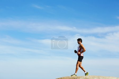 Photo for Male runner in sportswear running over sea rocks - Royalty Free Image