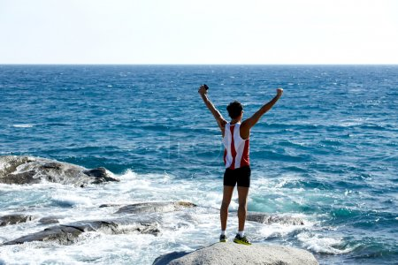 Photo for Runner get to the top of the high mountain and happy rising up his hands - Royalty Free Image