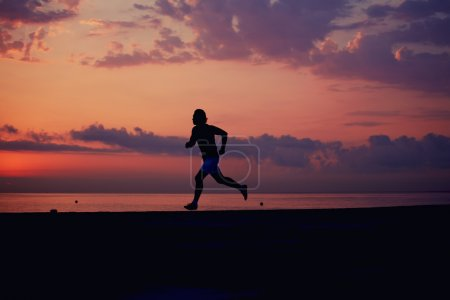 Photo for Fit man running into colorful sunset along the beach - Royalty Free Image