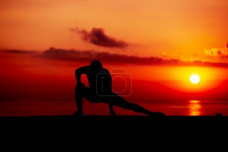 Photo for Silhouette of athletic build runner stretching the legs - Royalty Free Image
