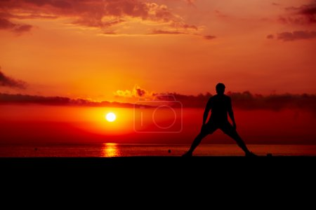 Silhouette of male athlete working out cross training on colorful sunrise background, beautiful silhouette of sportsman doing stretching exercise standing on the beach