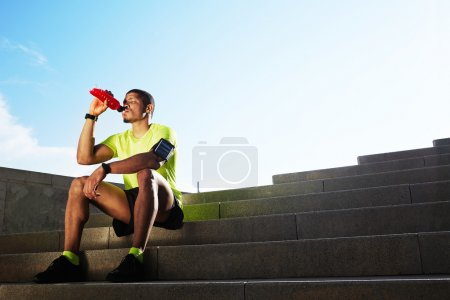 Handsome athletic runner seated on the steps drink water, beautiful fit man in bright fluorescent sportswear, sports fitness concept