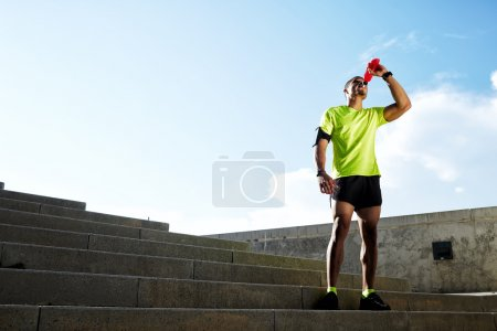 Dark-skinned runner drink water after intensive evening run, beautiful fit man in bright fluorescent sportswear, sports fitness concept