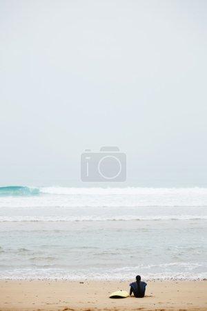 man in wetsuit taking a break after surfing