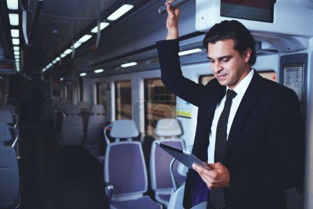 Mature handsome businessman working with digital tablet during going to work in train