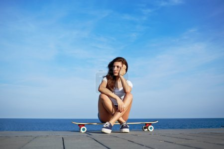 Beautiful sexy girl sits on longboard with amazing horizon of sea on background, young hipster girl posing at beautiful sunset light sitting on her skateboard, attractive woman enjoying sunny evening