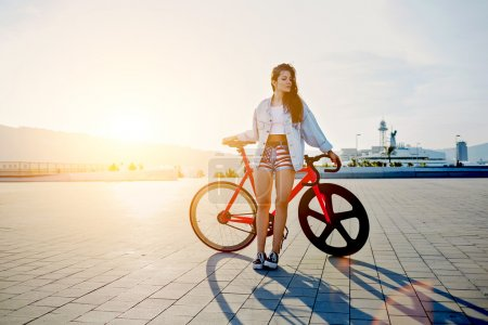 Photo pour Victoire de la jeune femme séduisante fixe gear bike posant à l'extérieur avec la douce lumière du coucher du soleil sur le fond, jolie jeune femme aux cheveux brune permanent avec sa bicyclette moderne rose au coucher du soleil, femme élégante hipster - image libre de droit