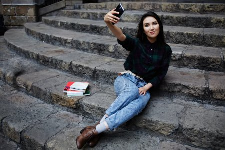 Young charming girl smiling while taking a self-ie outdoors,smiling student girl making a self portrait with smart phone sitting on steps, beautiful young hipster girl photographing herself with phone
