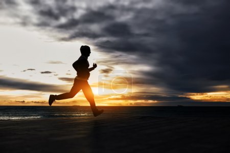 Photo for Silhouette of man running towards gold sun at cloudy dark sky background - Royalty Free Image