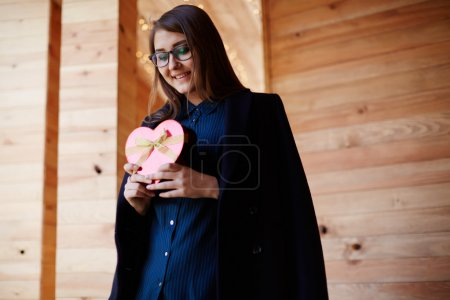 Woman holding red heart gift box