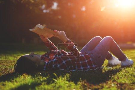 Photo pour Une jeune femme allongée sur l'herbe et lisant un livre, belle jeune fille lisant un livre alors qu'elle était allongée dans un champ d'herbe - image libre de droit