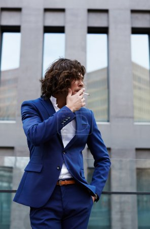 Young handsome businessman in stylish suit smokes a cigarette while standing outside the office