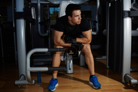 Young athlete seated on gym equipment