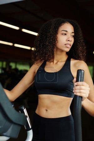 Photo pour Jeune modèle attrayant de fitness faisant de l'exercice sur une machine cardio dans un centre de fitness - image libre de droit