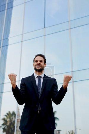 Photo pour Un homme excité avec l'esprit gagnant célébrant le succès, homme d'affaires heureux avec ses bras levés restant près de l'immeuble de bureaux, homme d'affaires ravi levant ses bras dans la victoire à l'extérieur d'un bâtiment de bureau - image libre de droit